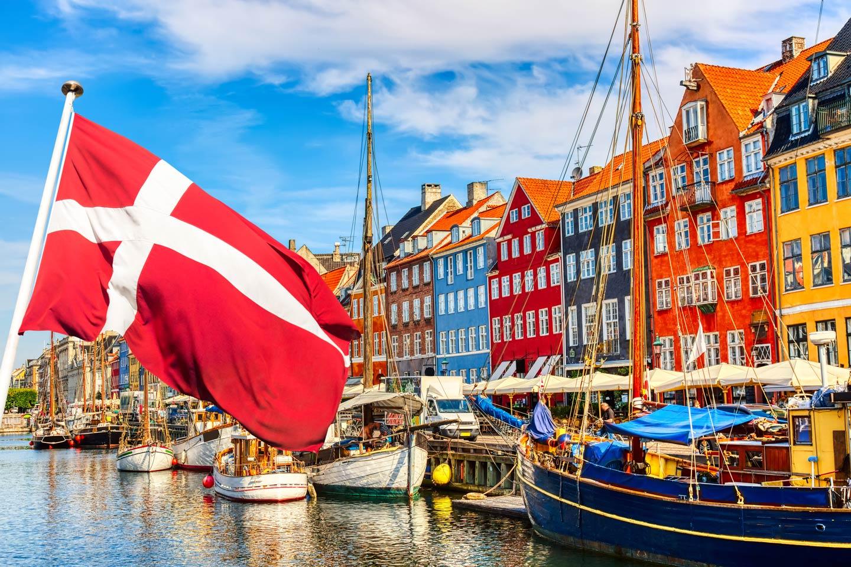 The Danish flag waving over the Nyhavn area of Copenhagen Harbor.