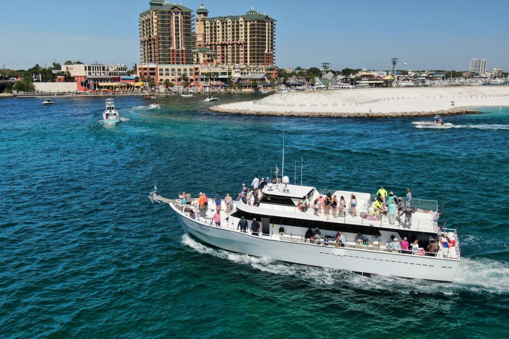 A large party fishing boat returning to Destin Harbor after a shared fishing charter