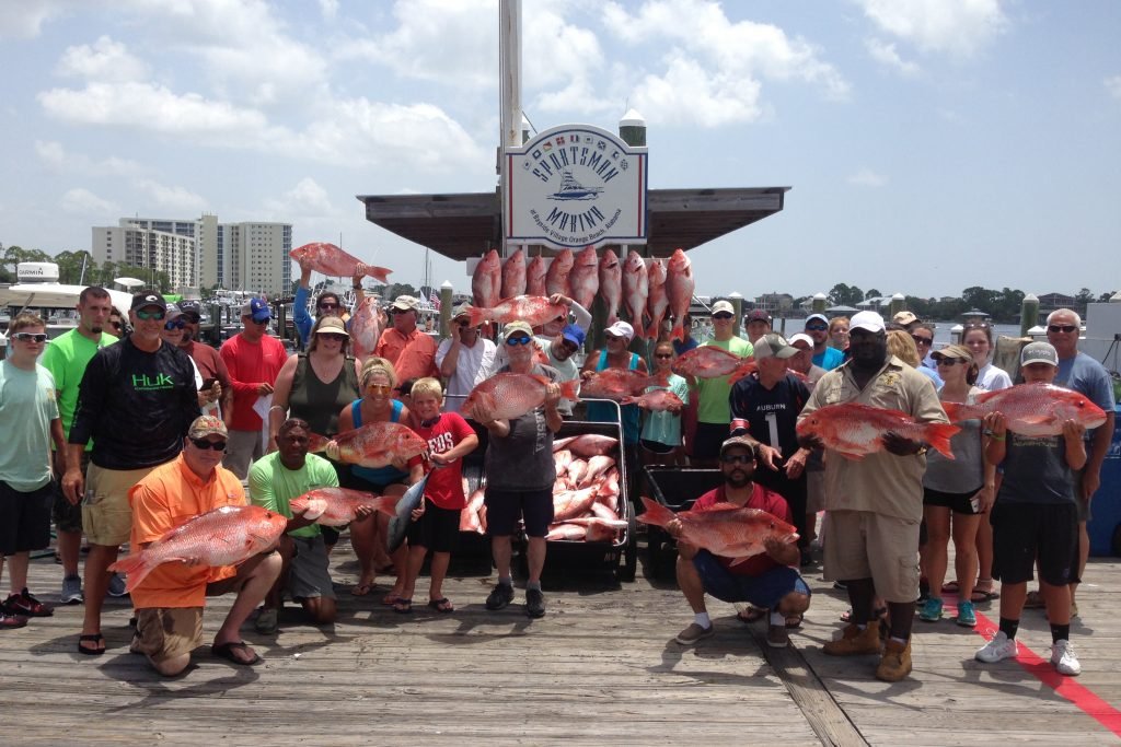 A large group of anglers posing with their fish at a dock after a party boat fishing charter in Orange Beach, AL