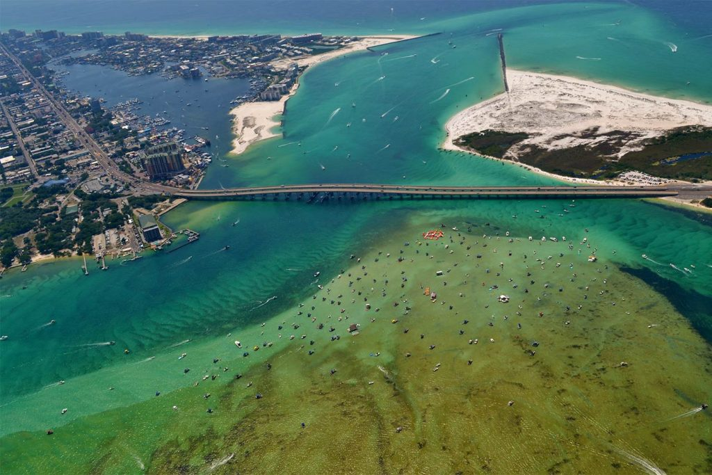 An aerial view of the Mid-Bay Bridge with destin on the left, surrounded by green waters full of boats