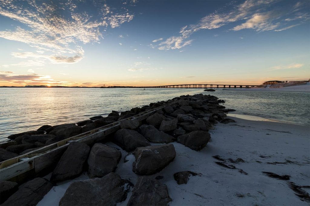 An image of the rocks looking towards Destin across the bay at sunset
