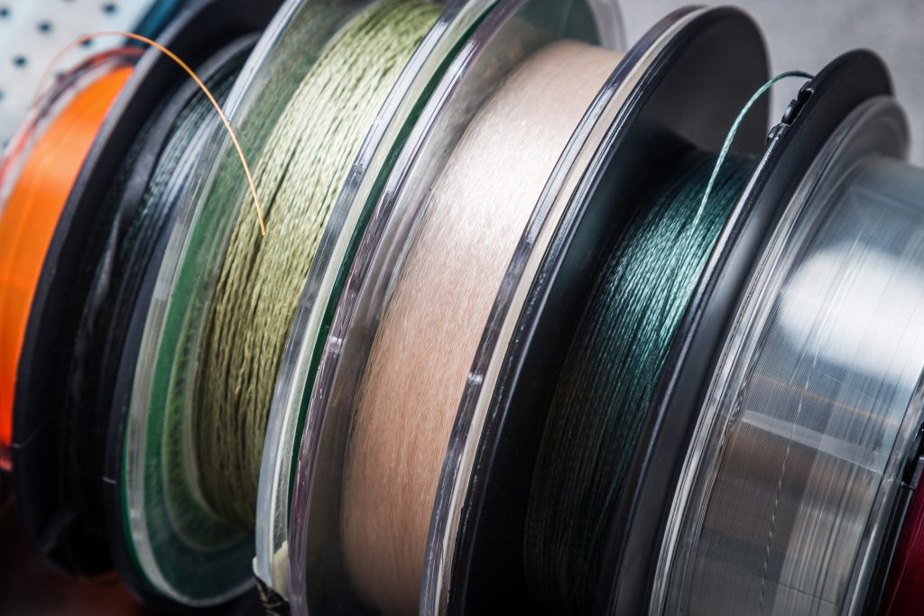 Spools of different types of fishing line next to each other