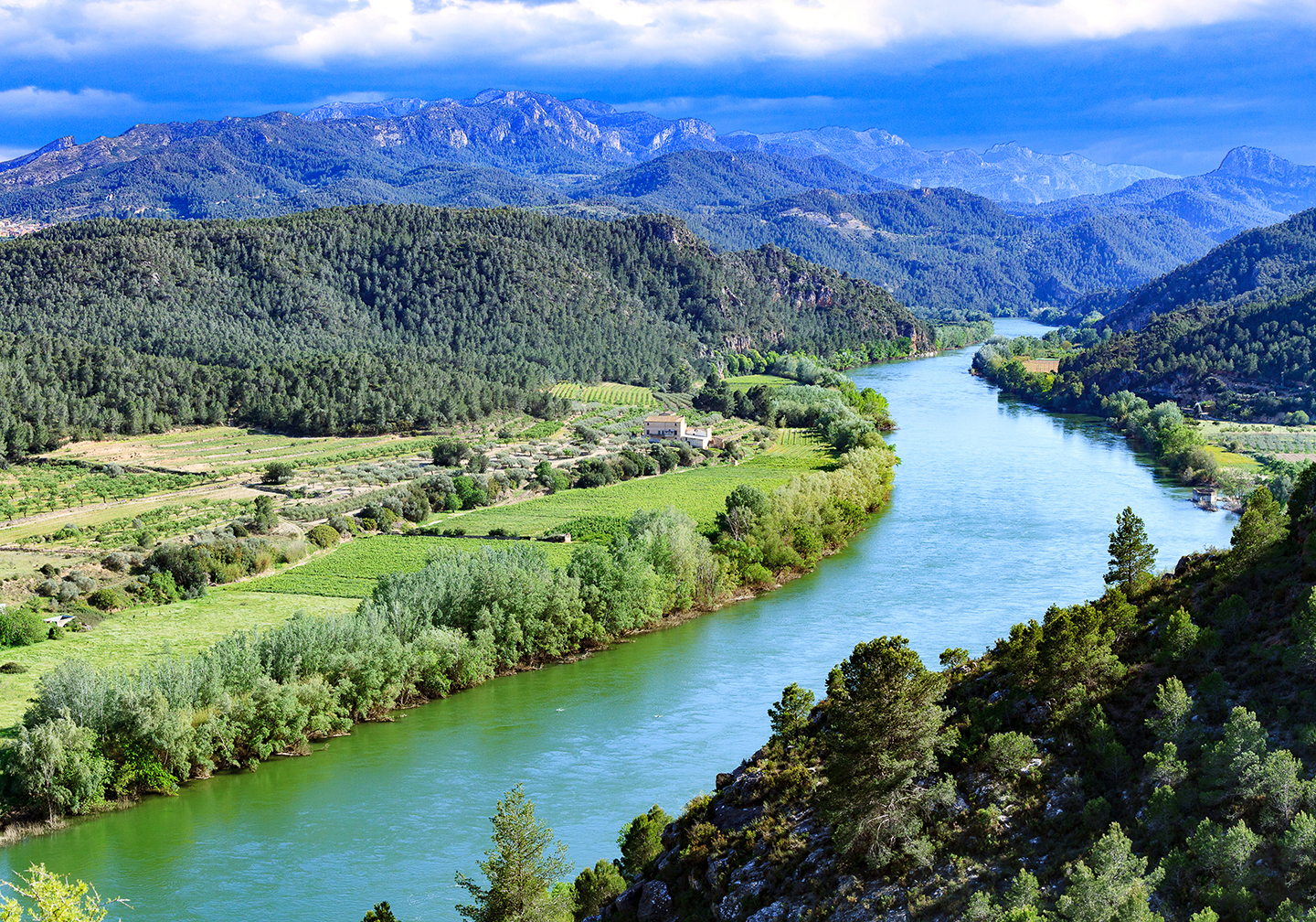 The Ebro River in Spain, with green fields on either side and blue mountains in the distance.