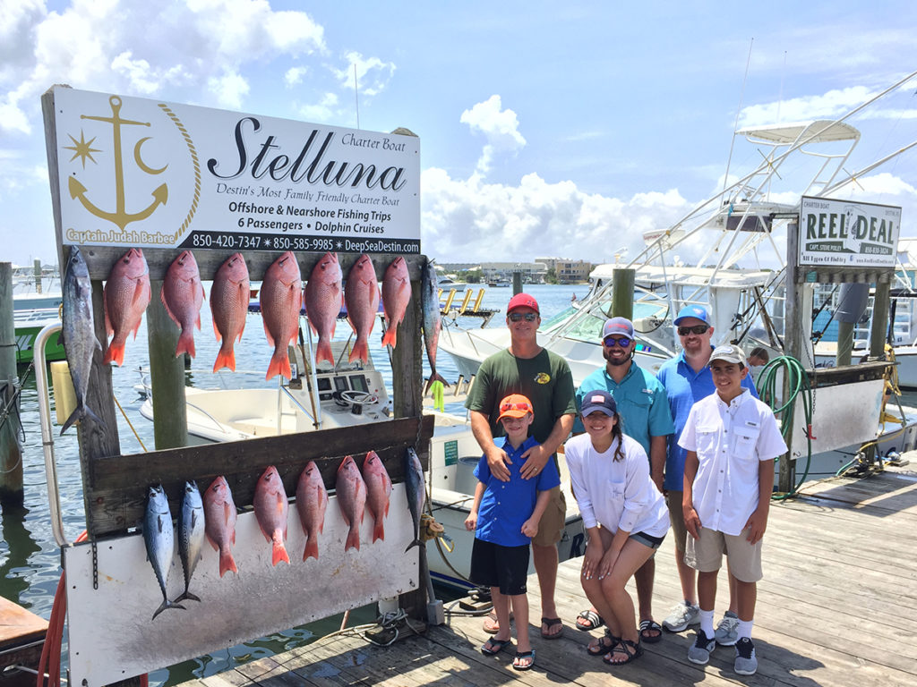 A family posing with their catch of Red Snapper and King Mackerel at the dock in Destin, Florida