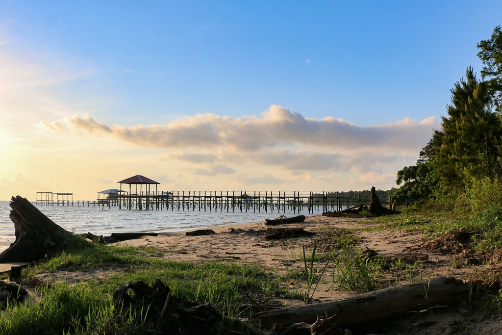 A pristine beach in Fairhope, Alabama, with an old fishing pier in the distance