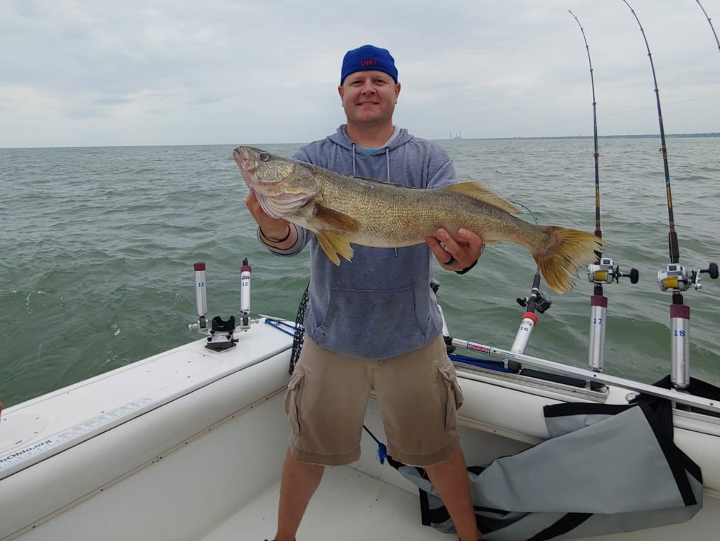 A smiling fisherman in a cap, standing on a boat holding a big Walleye