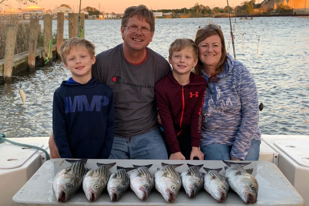 A family sits on the dock with their Chesapeake Bay Rockfish in front of them