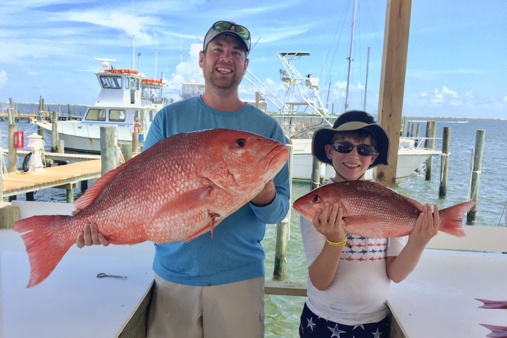A man and his son holding large Red Snapper at a dock in Orange Beach, AL