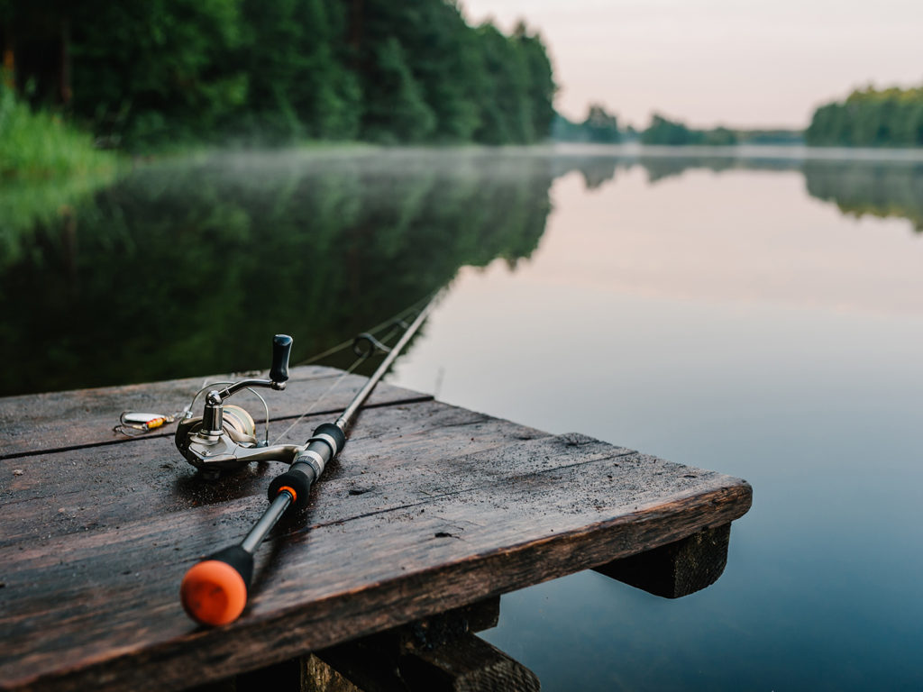 a finesse fishing rod lying on a wooden jetty by a lake