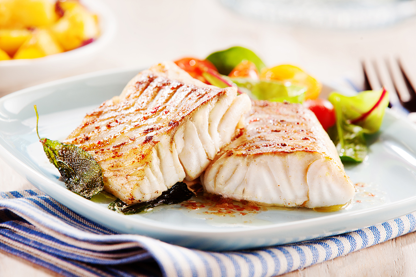 A healthy meal of grilled fish and vegetables served on a while place on a table