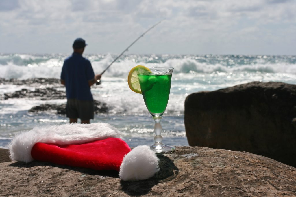 Fishing New Year's Day an angler fishing in the distance with a drink an a Santa's hat in the front