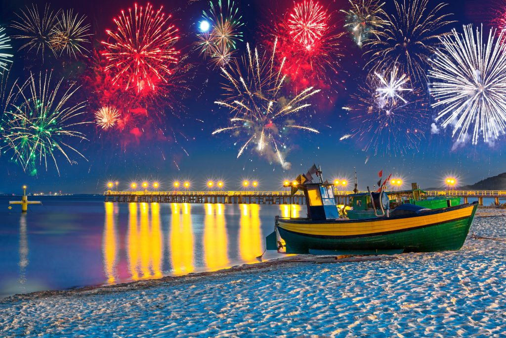 Fishing New Year's Eve: a fishing boat on a beach with fireworks in the background