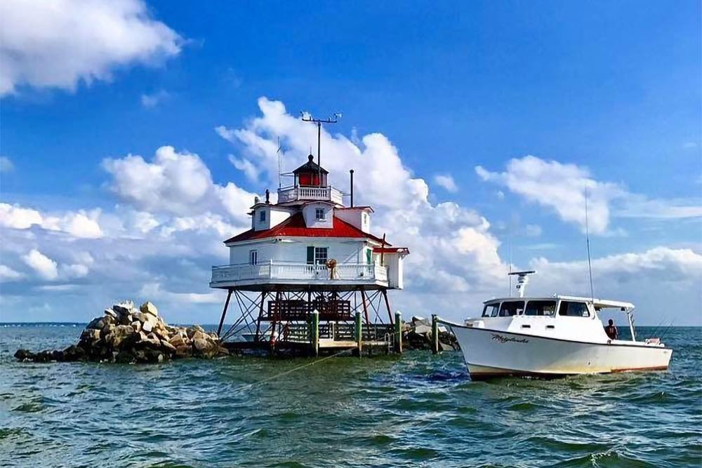 A fishing boat anchored next to a lighthouse in the Chesapeake Bay