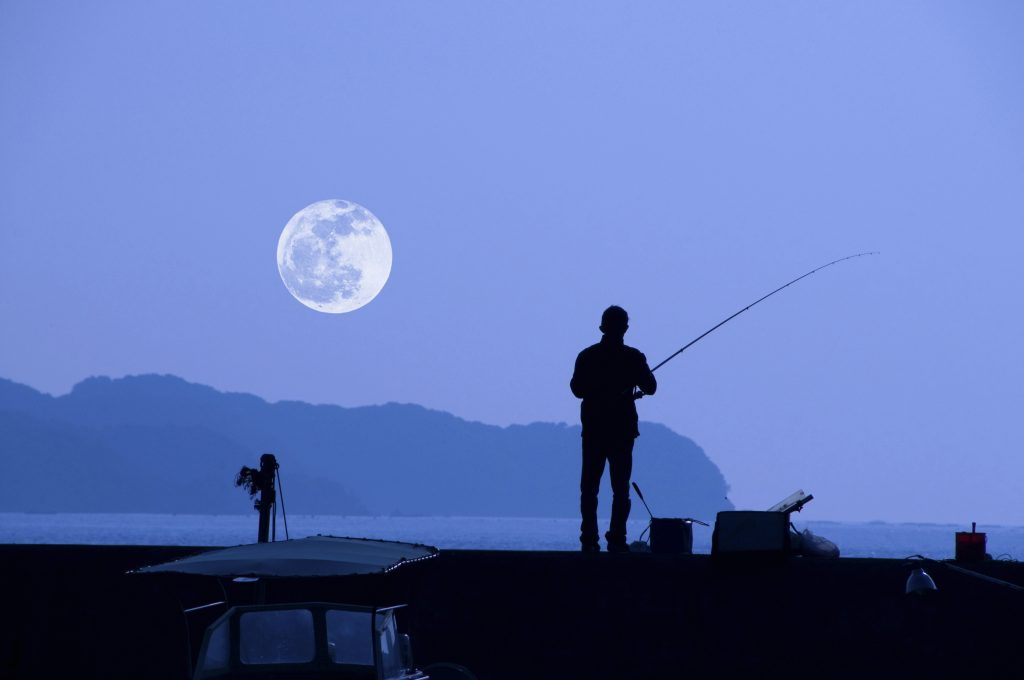 A fisherman casting his line from some rocks at night, with a full moon visible in the sky