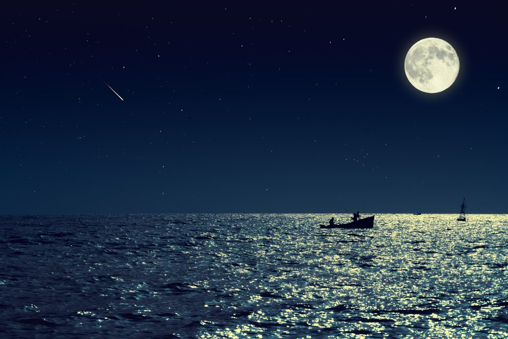 A small fishing boat on the sea at night under a full moon