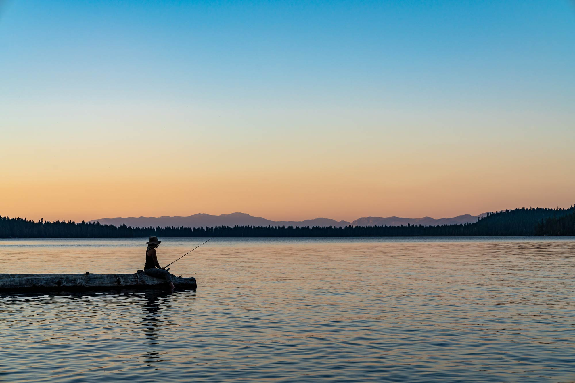 A woman fishing from a dock on Lake Tahoe