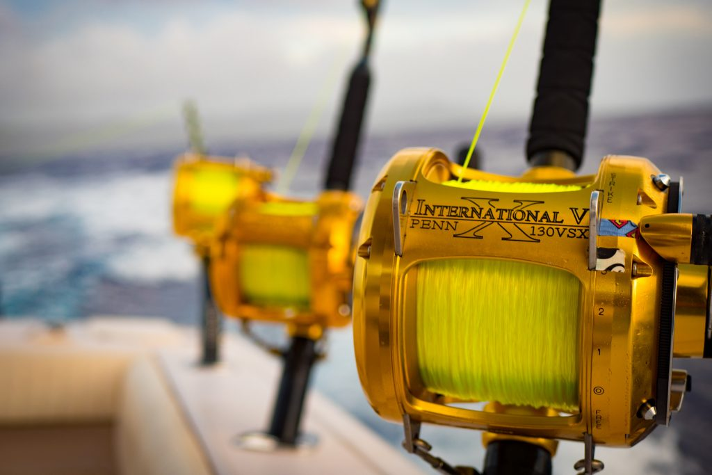 Three heavy trolling reels rigged with copolymer line on the side of a boat