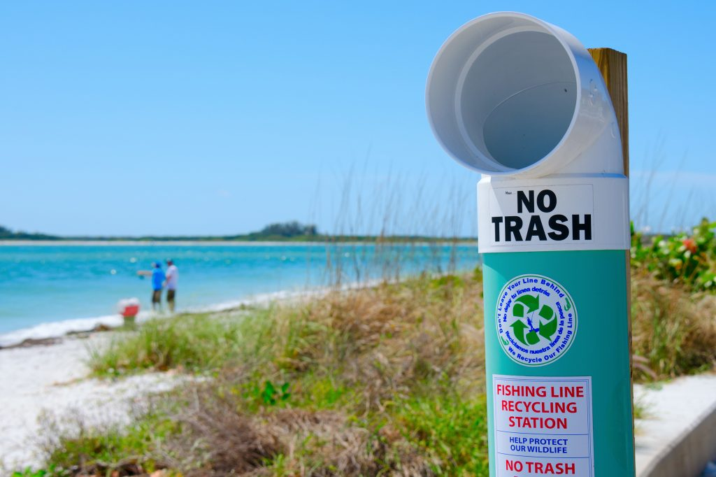 A fishing line recycling point on a beach. Two anglers are surf fishing in the background