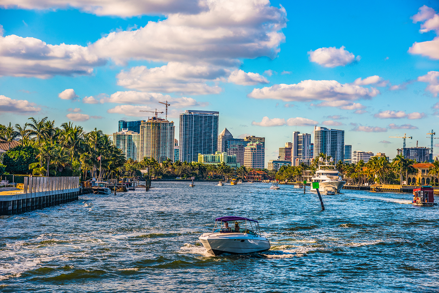 A boat coming towards you on the water with Fort Lauderdale downtown in the background.