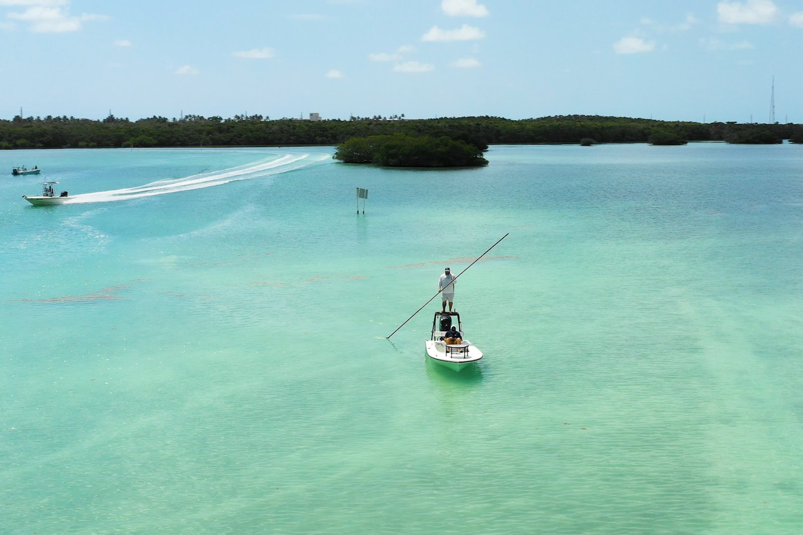 A man poling across shallow water on a flats fishing boat, with mangroves and another boat in the distance