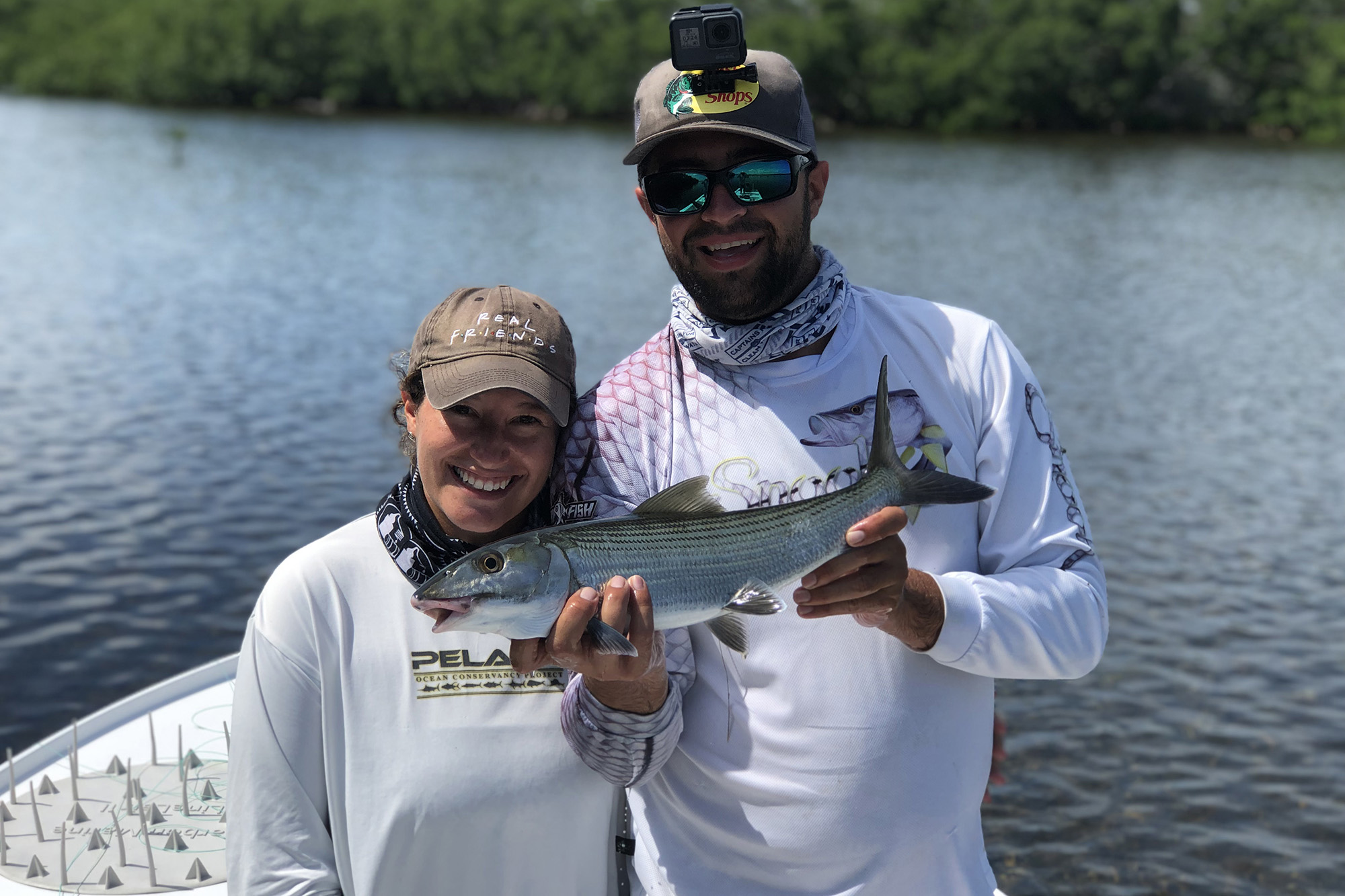 A couple holding a Bonefish on a sunny day, with water and vegetation behind them