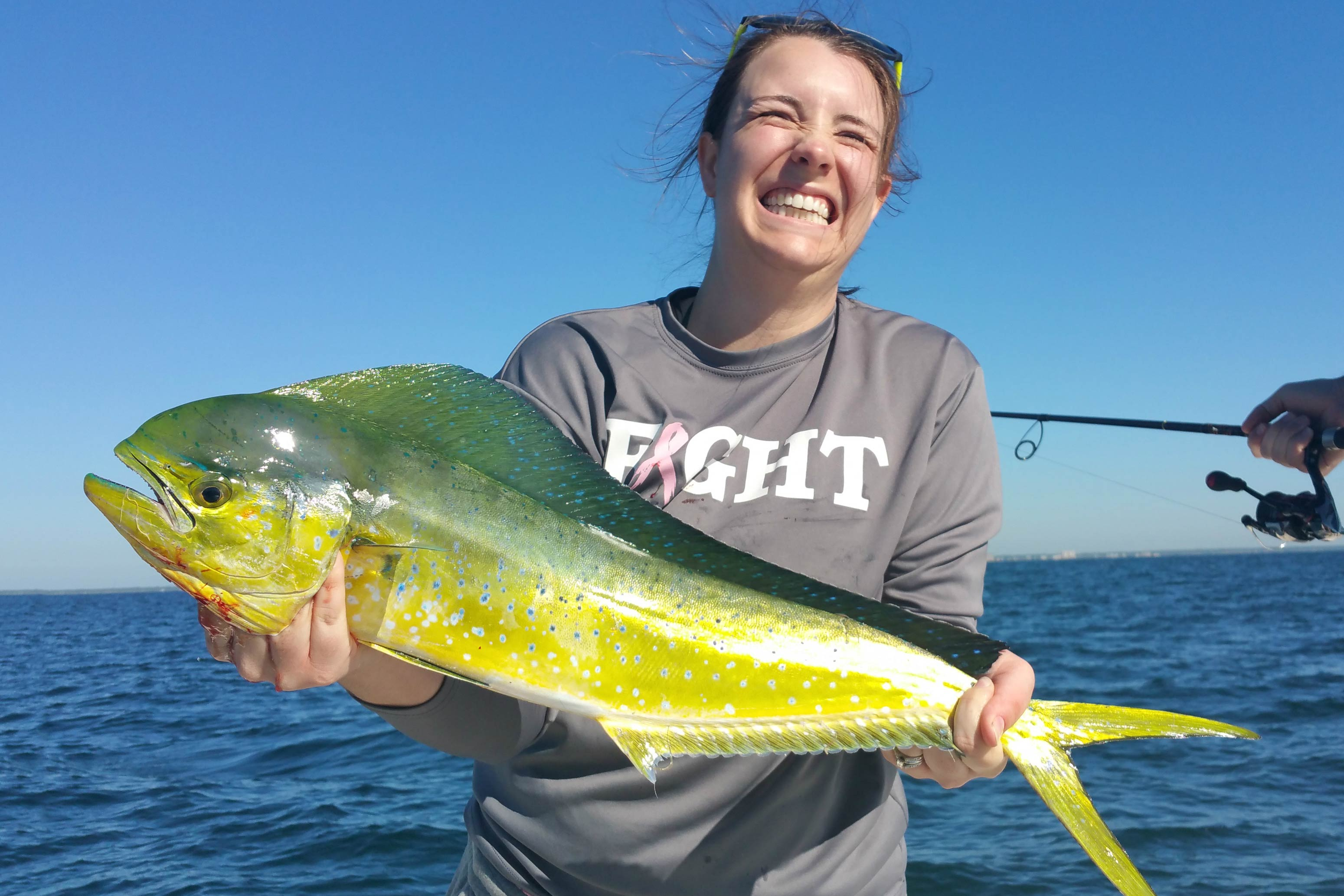A woman smiles as she holds a Mahi Mahi caught in Florida