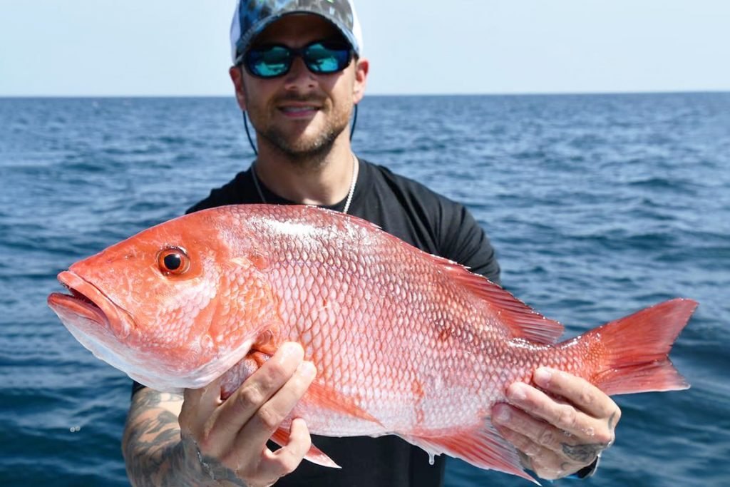 A man in sunglasses and a hat holding a Red Snapper with open sea behind him
