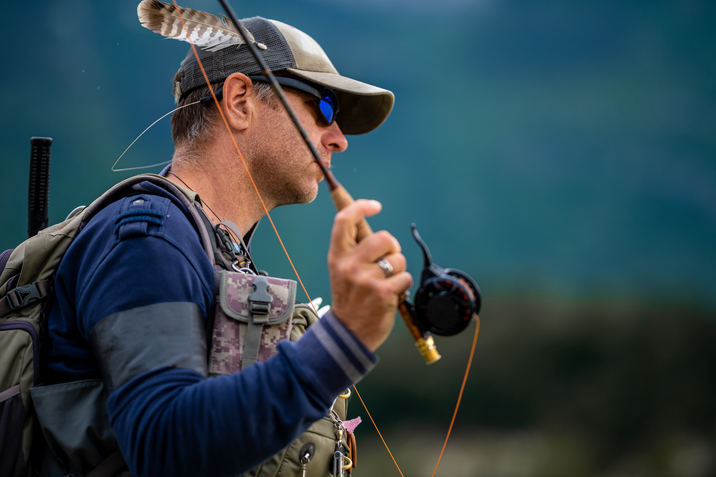 A man in a hat and sunglasses casting a fly rod