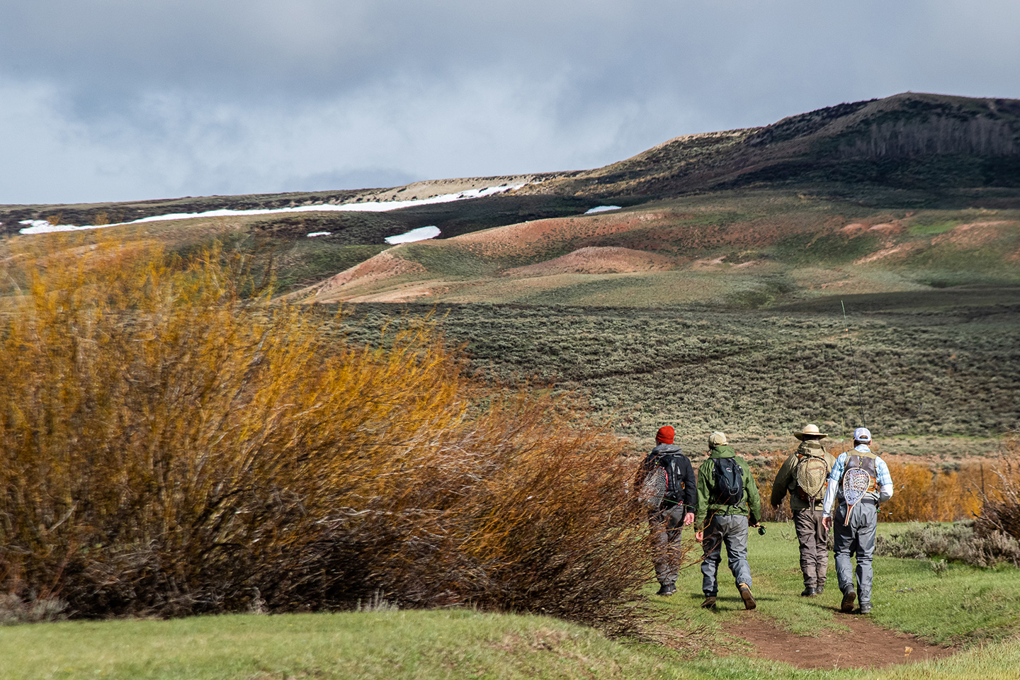 A group of fly fishers hiking out in remote countryside