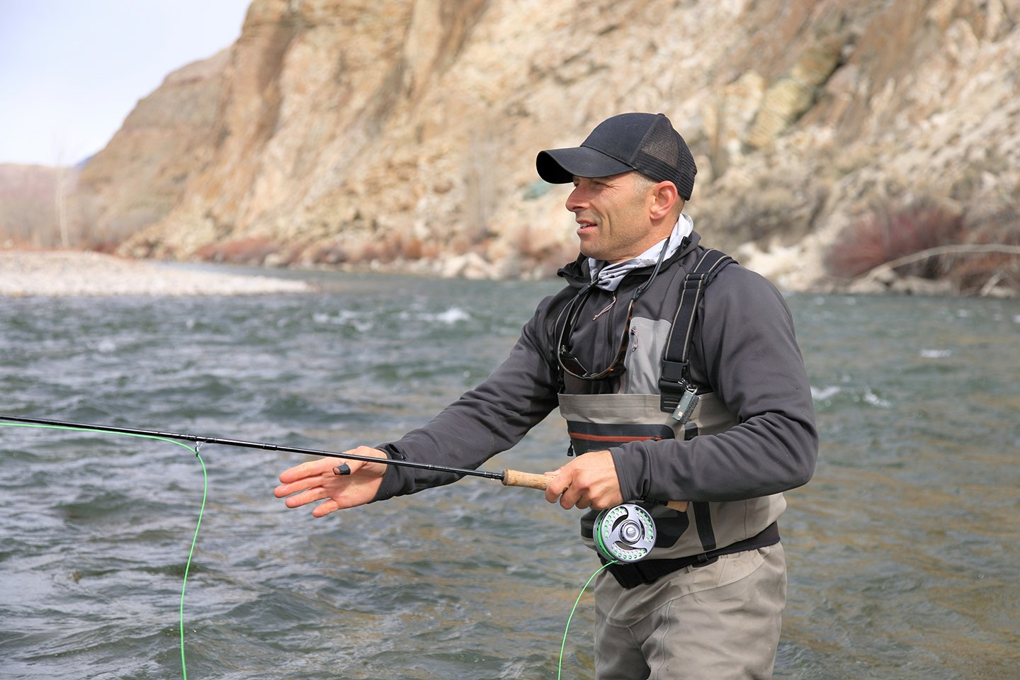 A fly fisherman focusing on his line while he tries to catch a fish