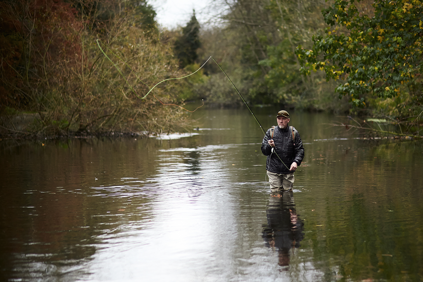 A fly fisherman wading in the River Wandle in Southwest London