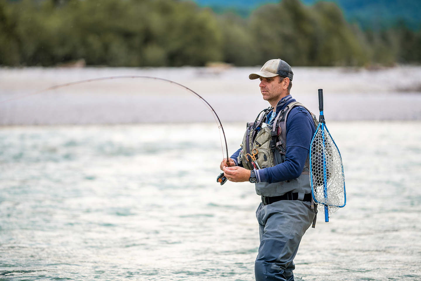 A veteran fly fishing in a river as part of a fishing therapy retreat