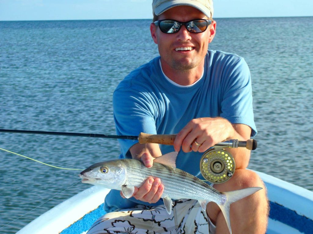 A smiling angler in a cap and sunglasses holding a Bonefish and a fly rod and sitting on a boat