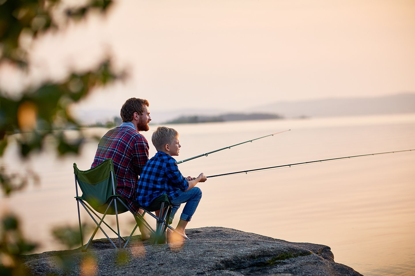 A father and son fishing together on the side of a lake