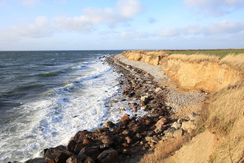Waves crashing against the rugged coastline on Funen Island.