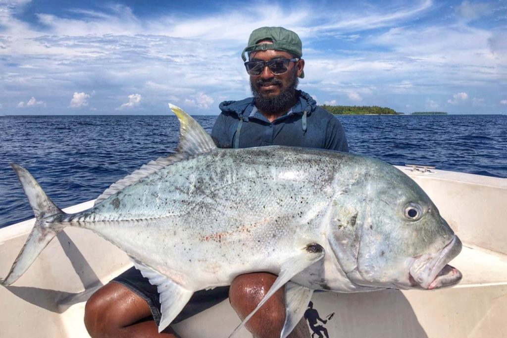 An angler holding a trophy Giant Trevally aboard a charter boat.