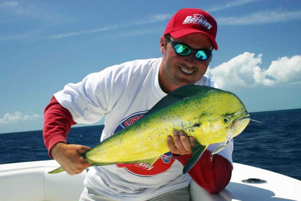 A man holds a Mahi Mahi up to the camera on a charter boat with the Gulf of Mexico behind him