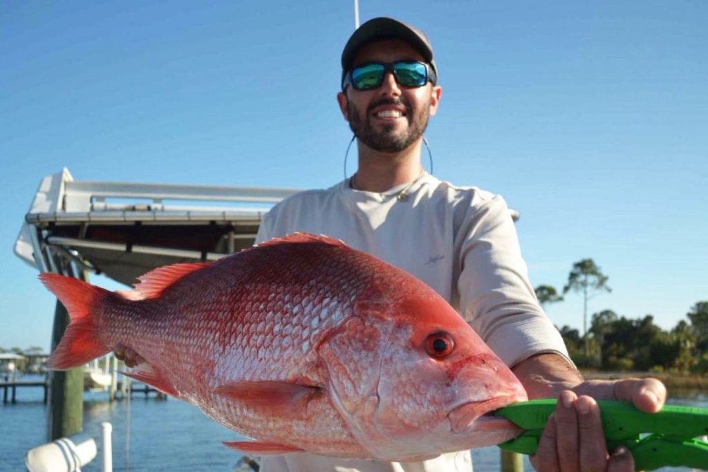 A man holds a large Red Snapper to the camera with a charter boat and the Gulf behind him
