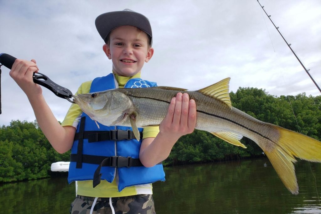 A child holds a Snook on a boat with the marshy waters of a Gulf bay behind him