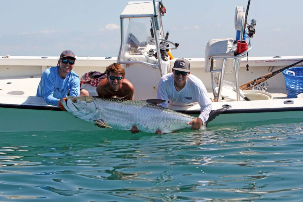 Three men lean from a shallow water vessel to hold a large Tarpon out of the water