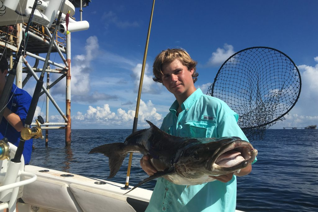 A young man holding a big Cobia caught while oil rig fishing in the Gulf of Mexico. An oil platform is visible in the sea behind him