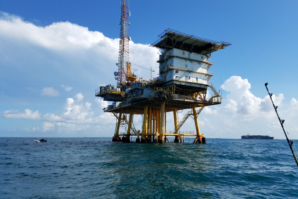 An oil platform in the sea, with a fishing rod in the bottom right of the shot