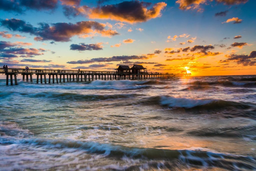 The sun sets over a fishing pier along the Gulf of Mexico