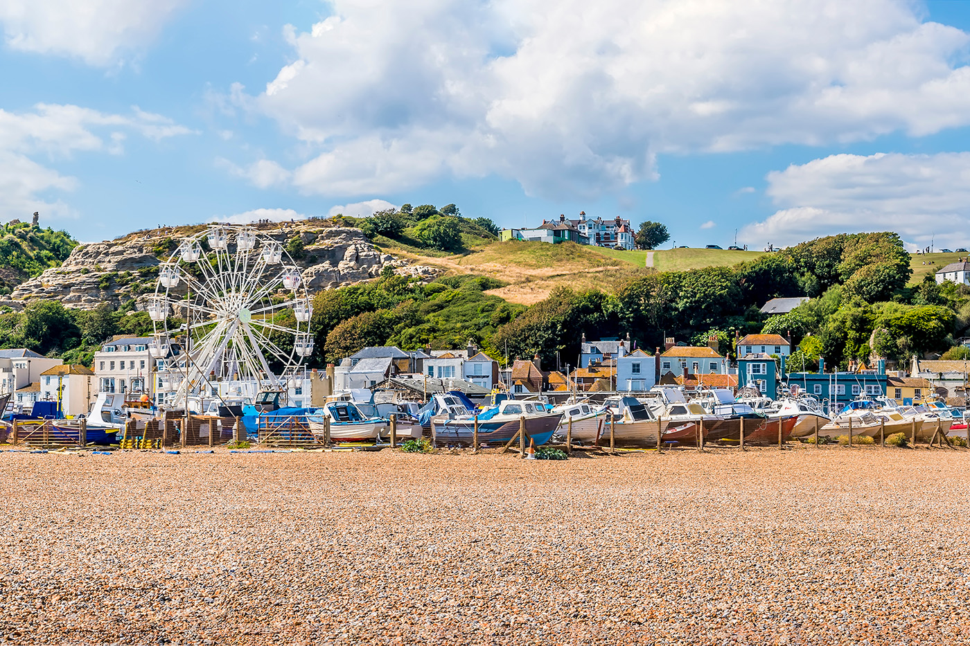 A view of Hastings Old Town from the beach, with fishing boats on the stones and cliffs in the distance