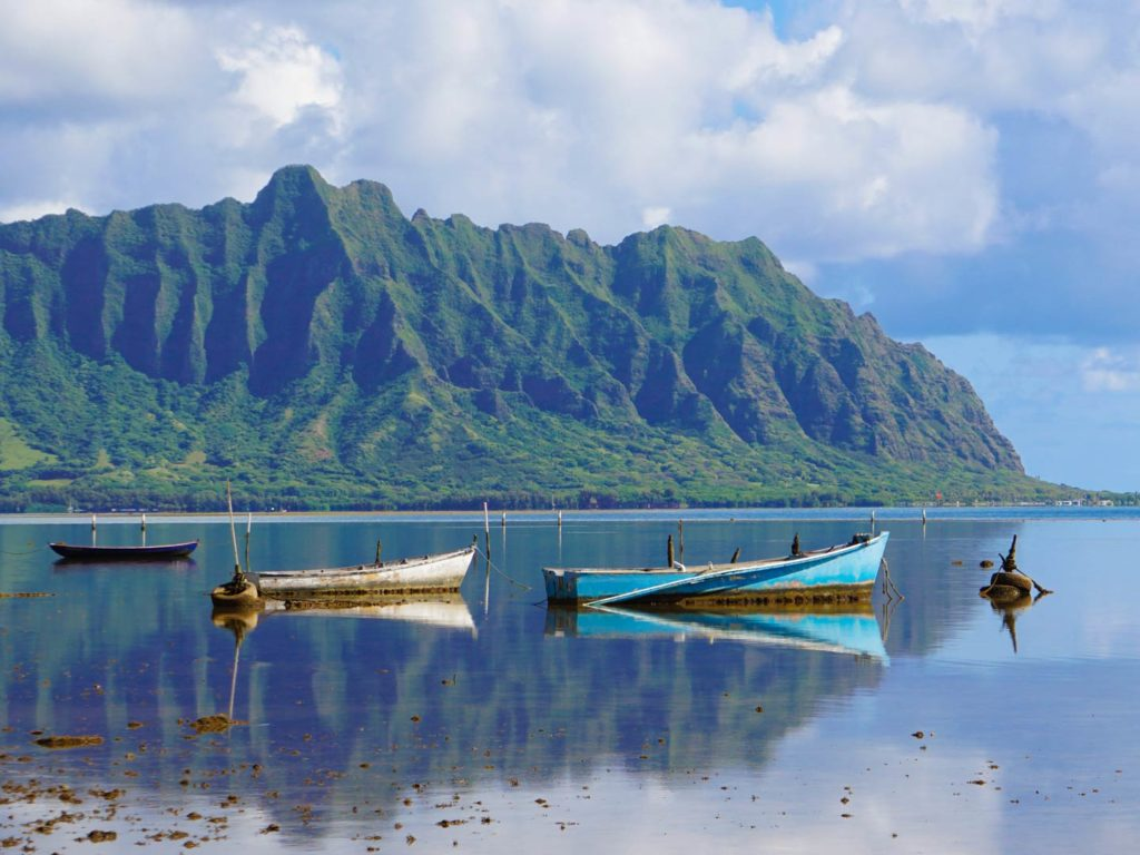 A view of some boats on the water with mountains in the background