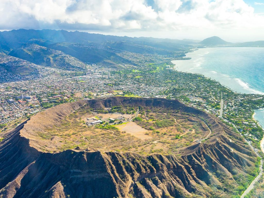 An aerial view of Hawaii island with a volcano crater and the ocean in view