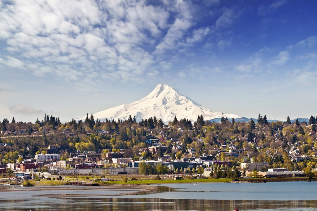 A view over the Columbia River of the town of Hood River, Oregon, with mount Hood visible in the distance