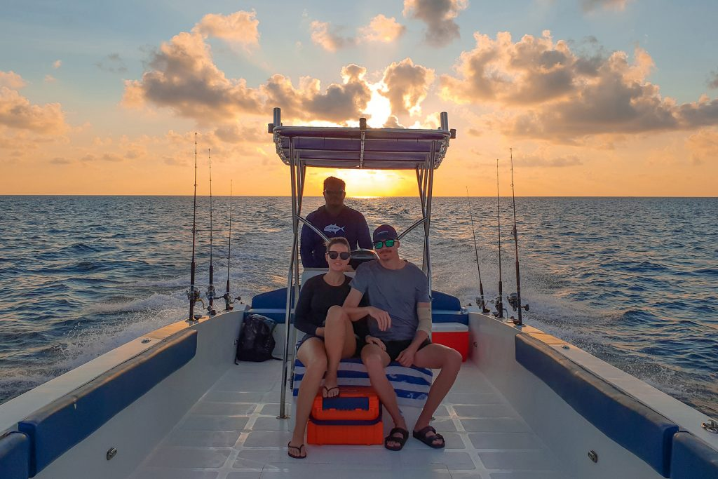 A couple sitting on a large center console boat on the ocean with the sun setting in the distance