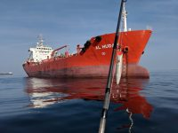 A large red oil tanker with a fishing rod and popping lure in the foreground