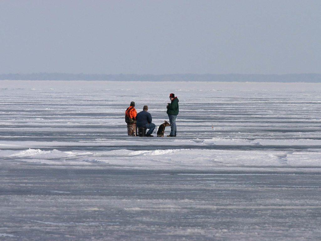 Men ice fishing on a frozen lake